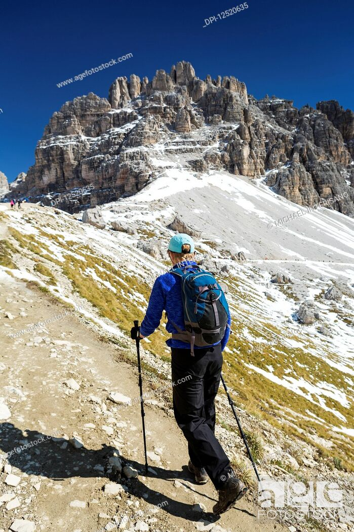 Stock Photo: Female hiker on steep trail with rugged mountain peaks and blue sky in the background; Sesto, Bolzano, Italy.