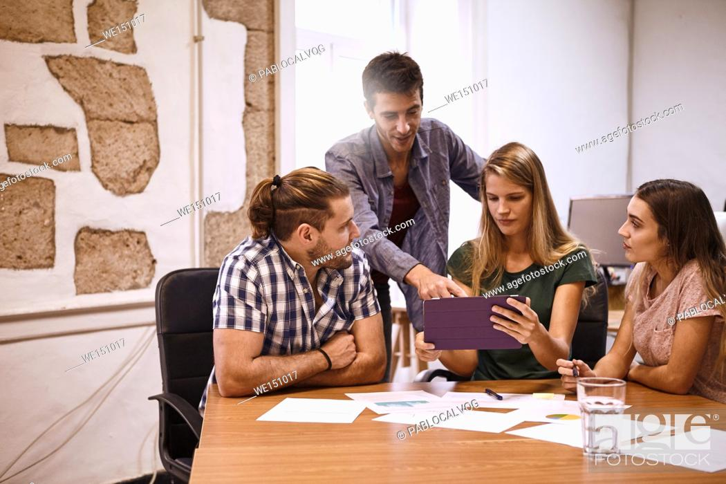 Stock Photo: Team of four young professionals in an interesting and captivating strategic discussion in a room with a conference table strewn with notes and tablet pc.