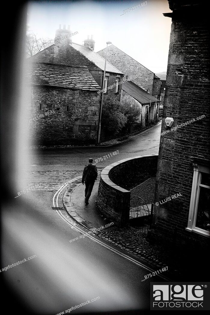 Stock Photo: View through a window of a street with a man walking in Grassington, Yorkshire Dales, England, UK, Europe.