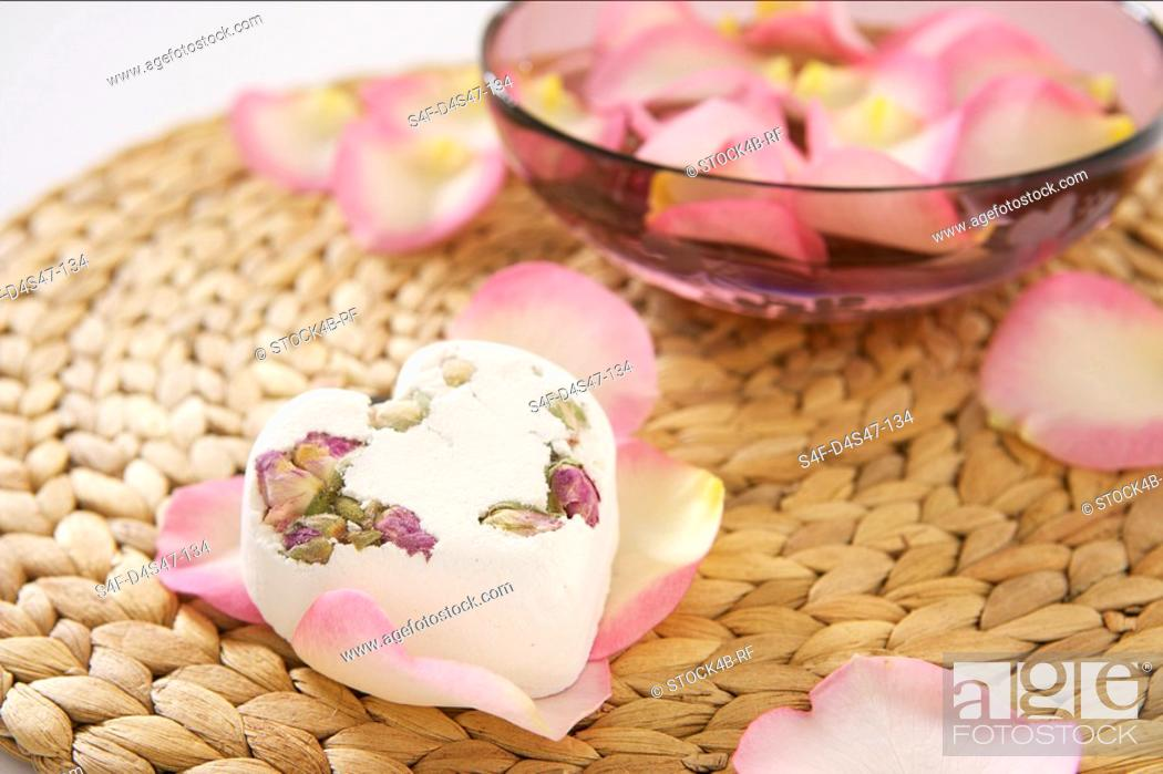Stock Photo: A heart-shaped piece of soap on rose petals.