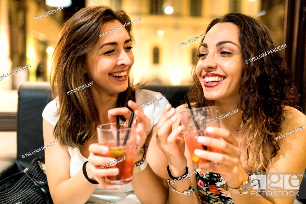 Stock Photo: Young women enjoying cocktail on night out.