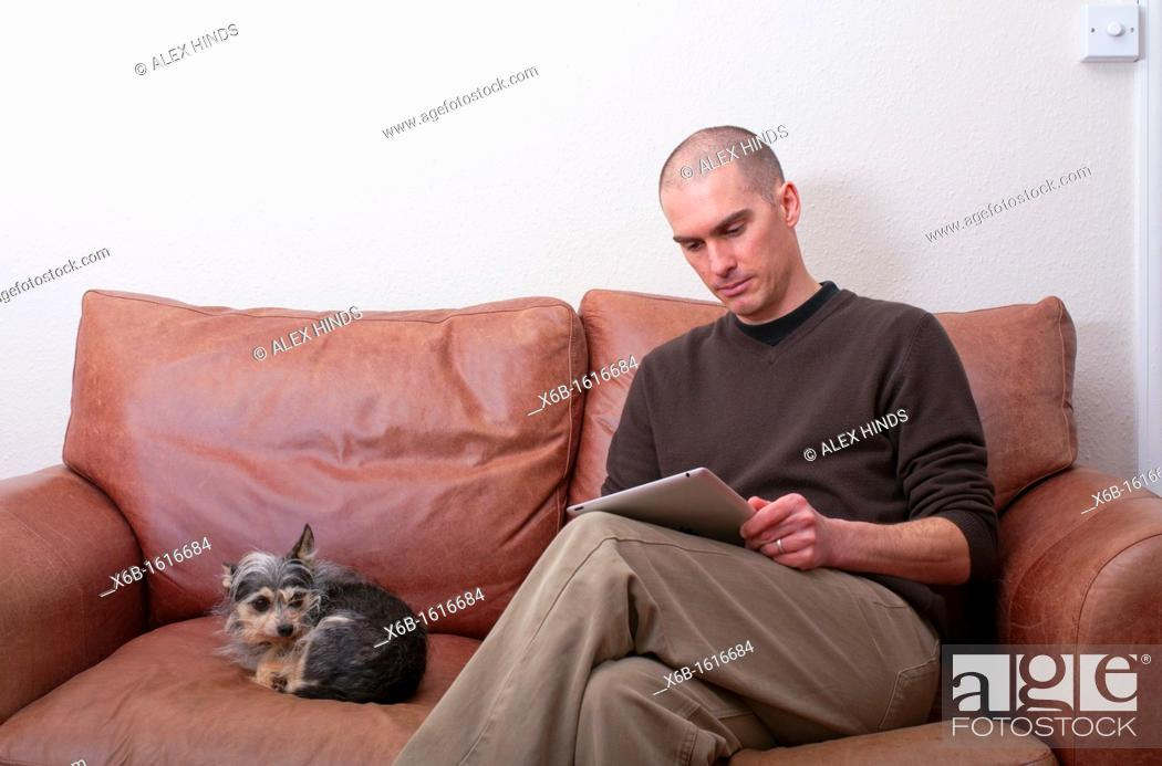 Stock Photo: forty year old man using ipad tablet in casual setting.