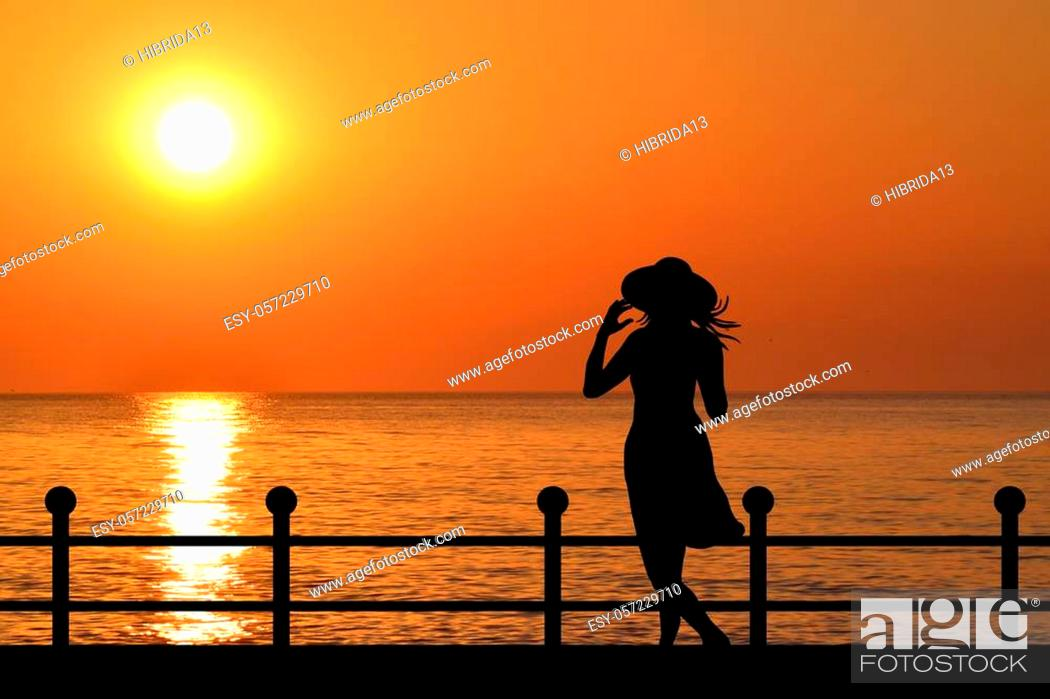 Stock Photo: Silhouette of a woman with hat on the waterfront at sunrise.