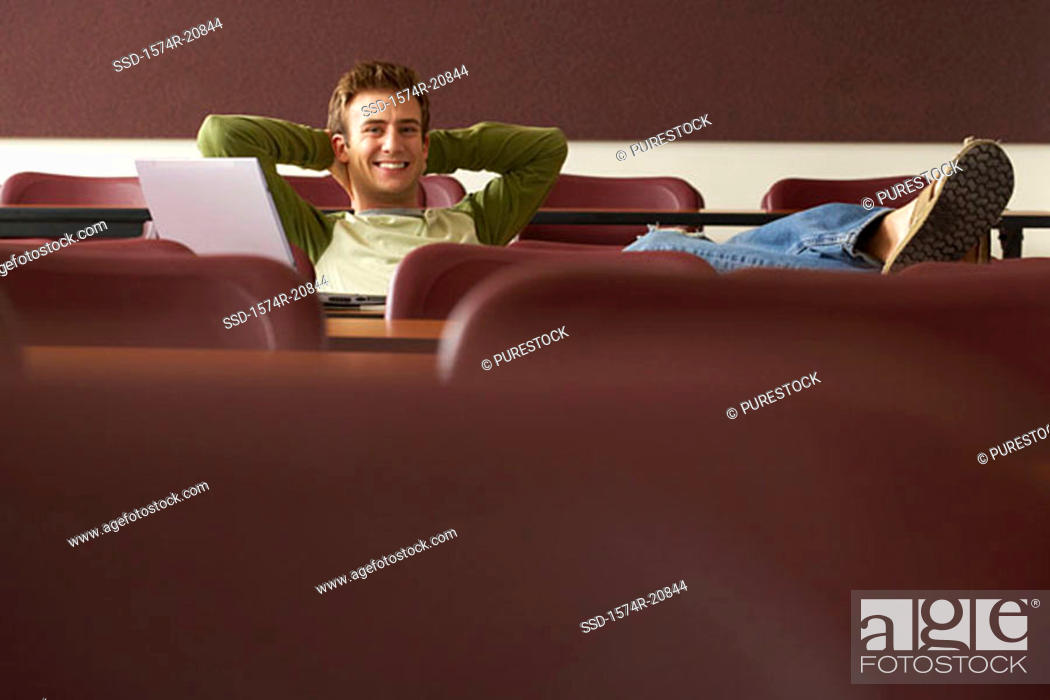 Stock Photo: Portrait of a college student sitting in a lecture hall with his hands behind his head.