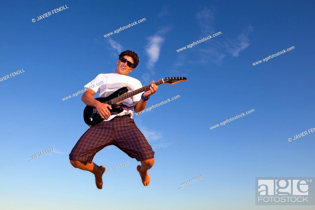 Stock Photo: Young man jumping with electric guitar.