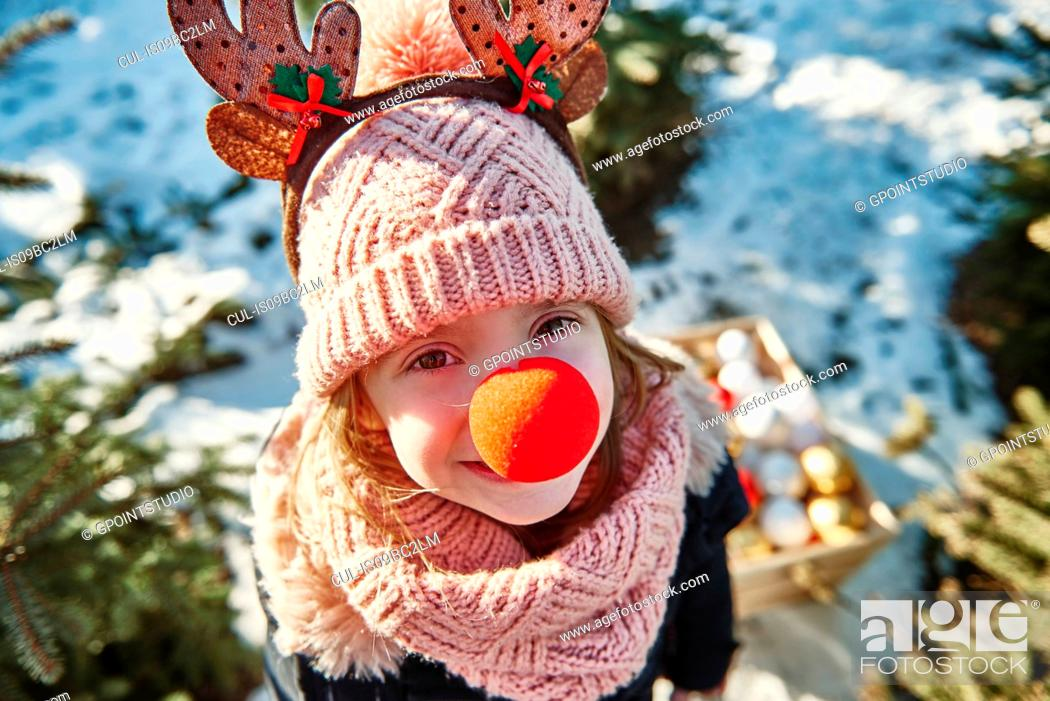 Stock Photo: Girl in christmas tree forest with red nose, high angle portrait.