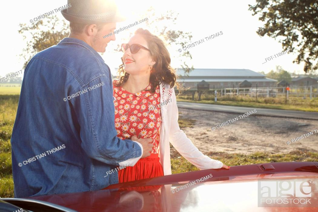 Stock Photo: A flirtatious rockabilly couple standing next to a vintage car.