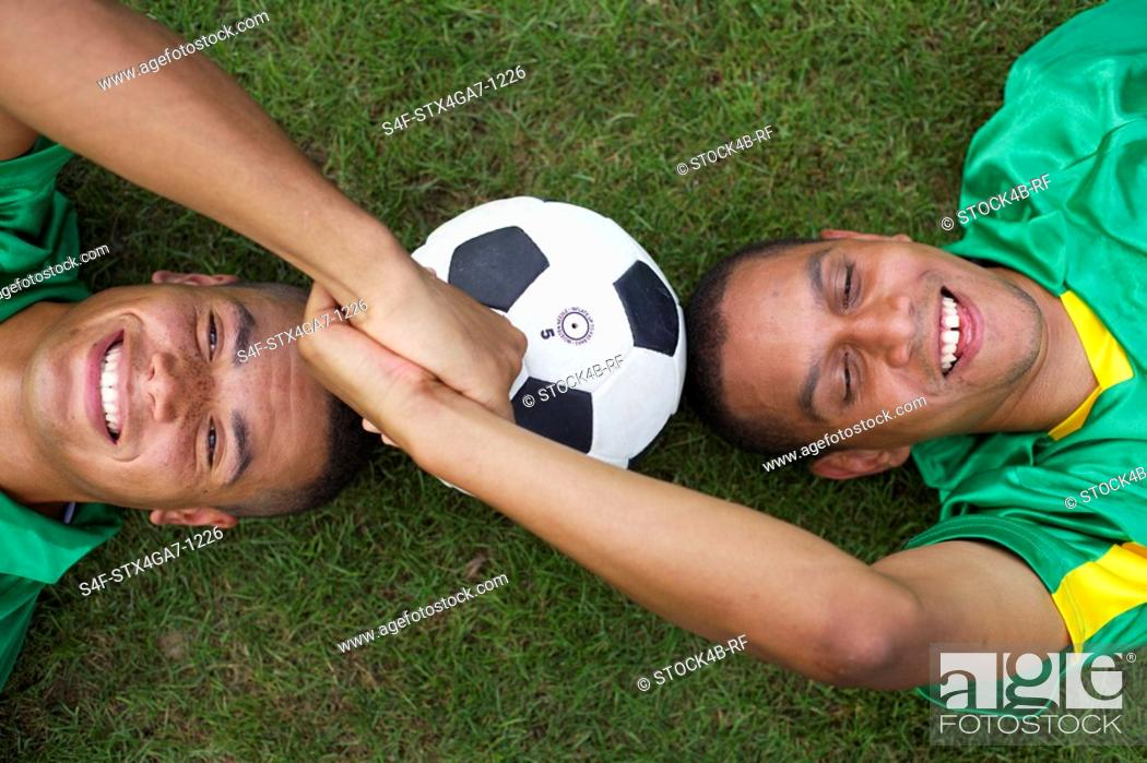 Stock Photo: Two Brazilian kickers lying on grass, holding hands.