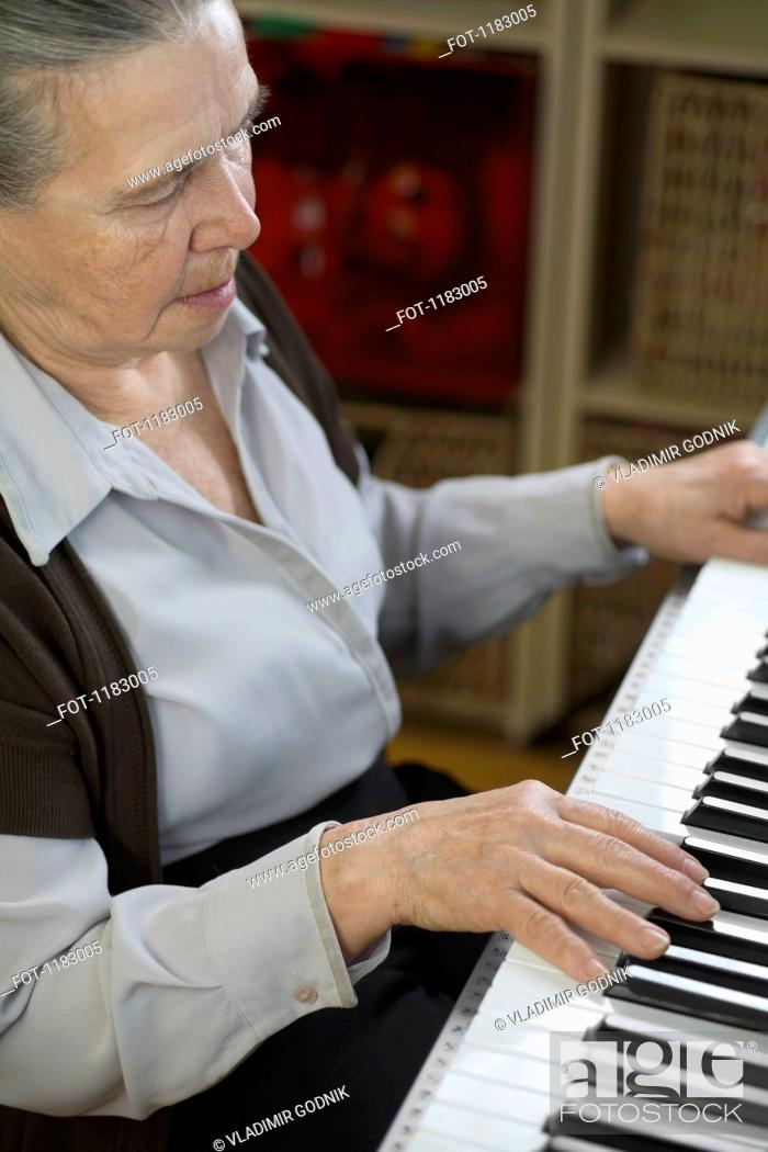 Stock Photo: A senior woman playing an upright piano.