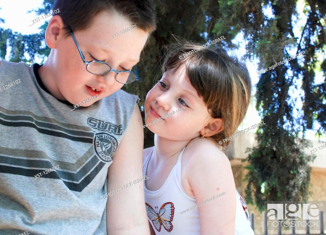Stock Photo: Young sister of 5 looks admiringly at her older brother of 7 model release available.