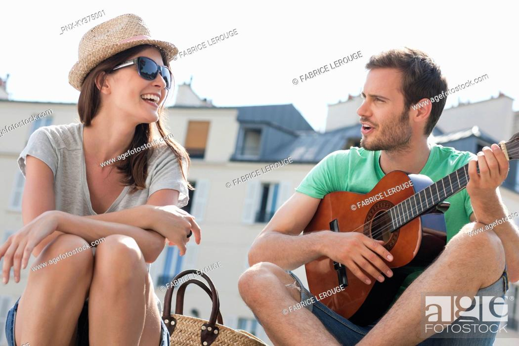 Stock Photo: Man playing a guitar with a woman smiling, Canal St Martin, Paris, Ile-de-France, France.