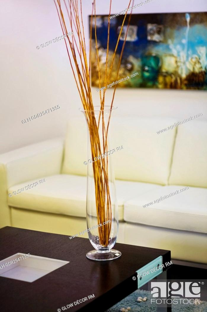 Photo de stock: Vase on a table in front of a couch.