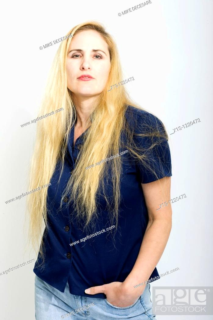 Stock Photo: Attractive blond American woman wearing blue jeans and a dark shirt has one hand in a pocket and looks at the camera.