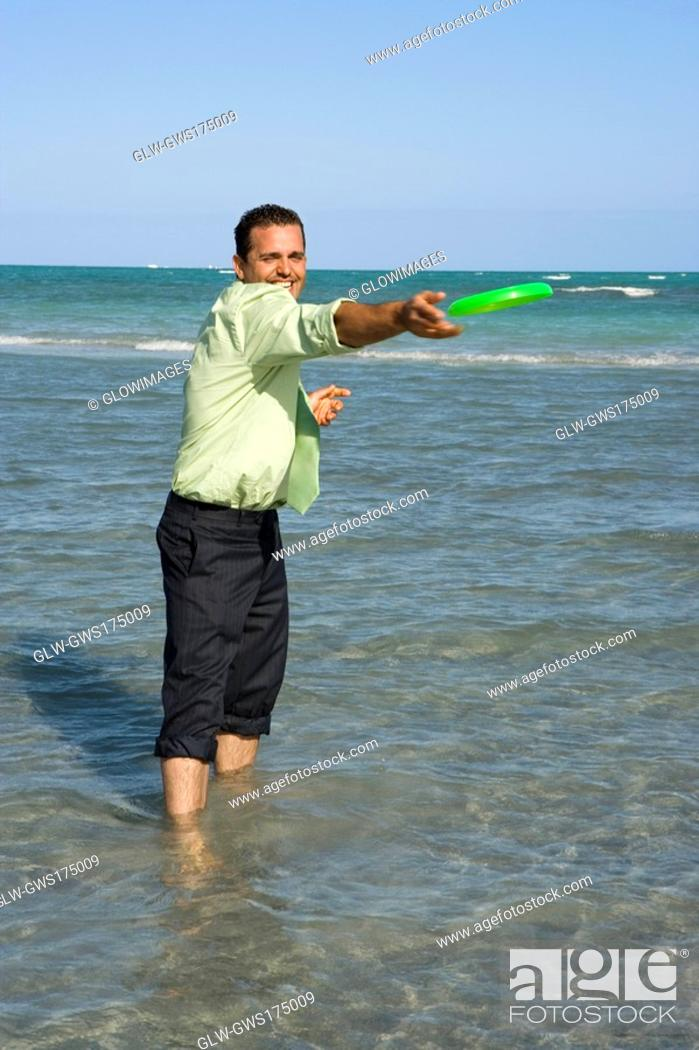 Stock Photo: Mid adult man playing with a plastic disc on the beach.