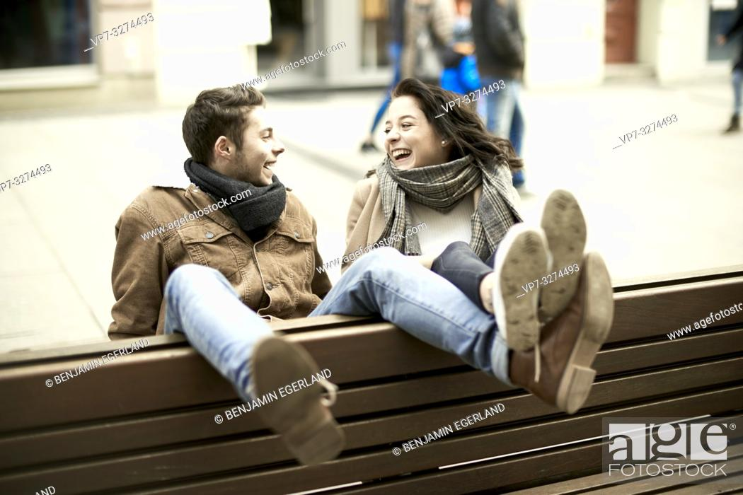 Stock Photo: young unconventional teenage couple sitting on bench the wrong way round in city, hanging out together, legs up, upside down, in Cottbus, Brandenburg, Germany.