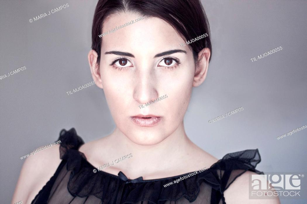 Stock Photo: Close-up portrait of a young woman with pale skin and dark hair looking at the camera.