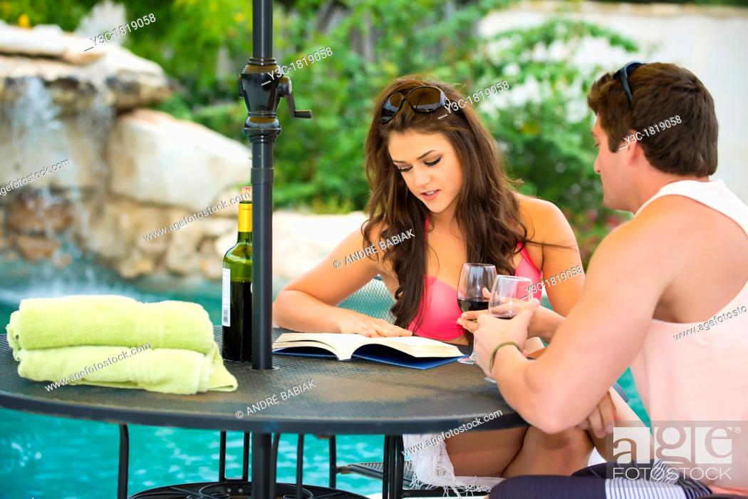 Stock Photo: Young couple sitting at a table in a vacation resort's swimming pool area reading and enjoying wine.