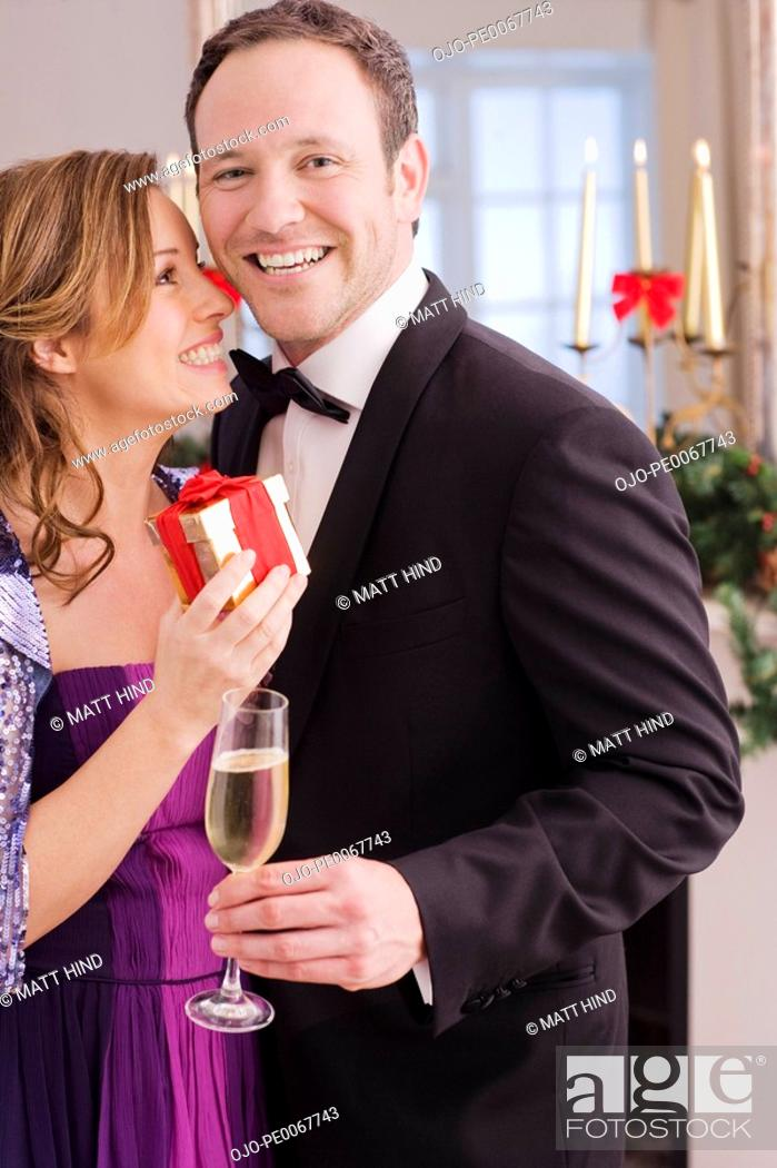 Stock Photo: Well dressed couple holding gift and champagne.
