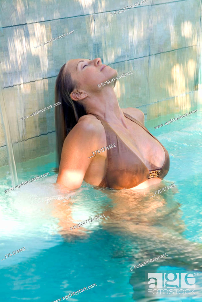 Stock Photo: Woman relaxes in pool and rinses her hair in the waterfall.