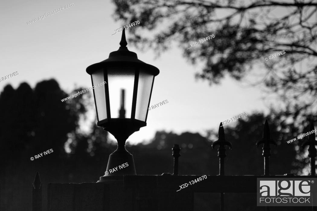 Stock Photo: Classic styled outdoor gate lantern highlighted by sunlight at dawn  Silhouette  Black and White.