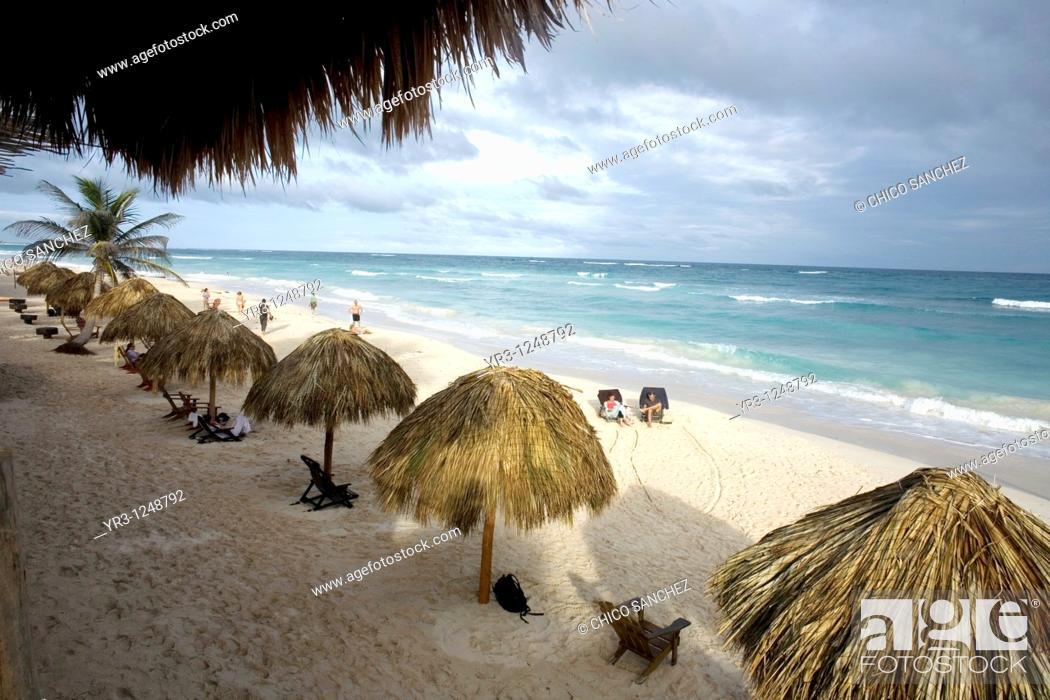 Stock Photo: Tourists gather on a beach along the Mayan Riviera in the ancient Mayan city of Tulum in Mexico's Yucatan Peninsula.