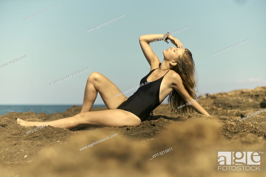 Photo de stock: woman in one-piece swimsuit lying on rocks at beach, enjoying sunny weather and summer holiday in Crete, Greece.