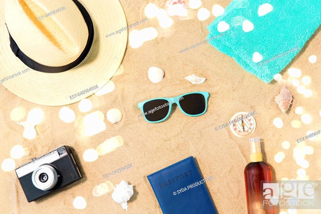 Stock Photo: camera, passport, sunglasses and hat on beach sand.