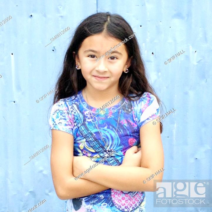 Stock Photo: Little girl smiling with her arms crossed looking at the camera.