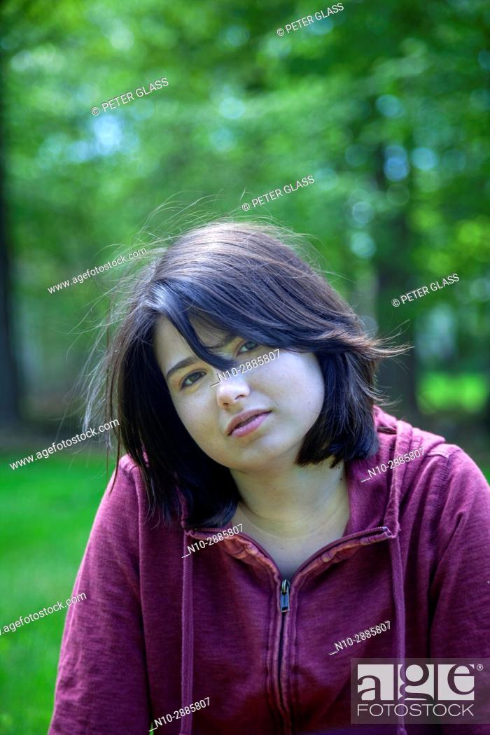 Stock Photo: Young woman, wearing a red sweatshirt, in front of trees in a park.