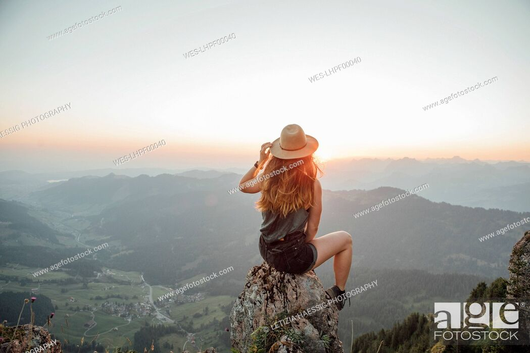 Stock Photo: Switzerland, Grosser Mythen, young woman on a hiking trip sitting on a rock at sunrise.