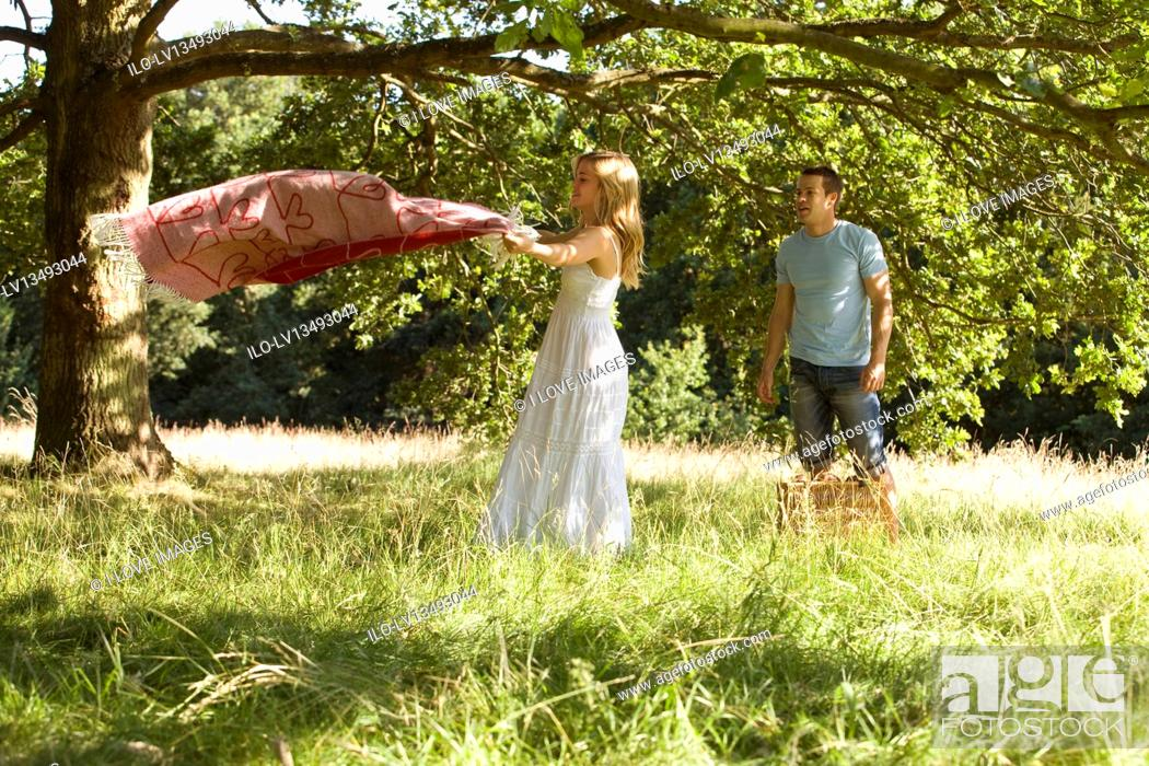 Stock Photo: A young couple laying a picnic blanket on the grass.