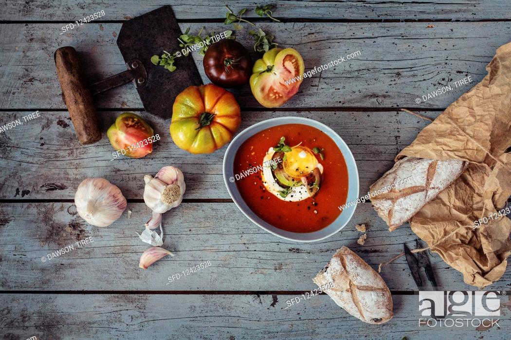 Stock Photo: Tomato soup with heritage heirloom tomatoes, cream, baby basil, cracked black pepper and garlic and rustic bread.