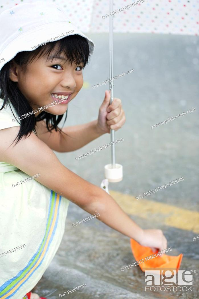 Stock Photo: Young girl outdoors in rain with umbrella playing with paper boat.
