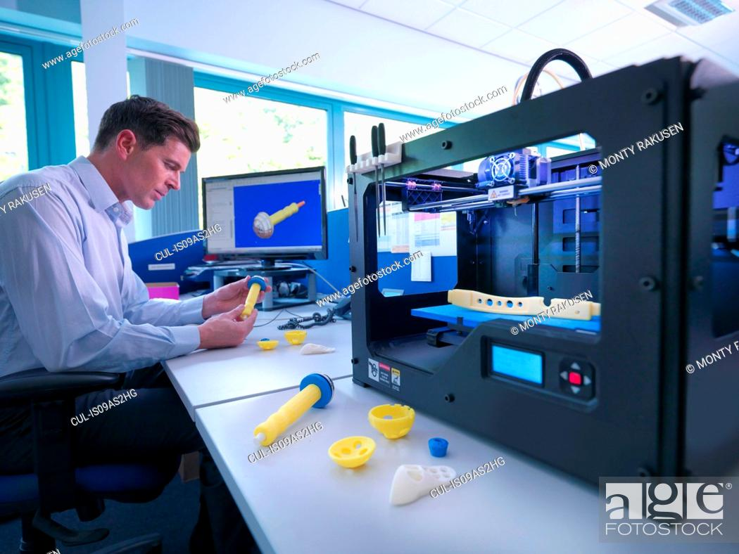 Stock Photo: Medical product designer with 3D printing machine with CAD design on screen in orthopaedic factory.
