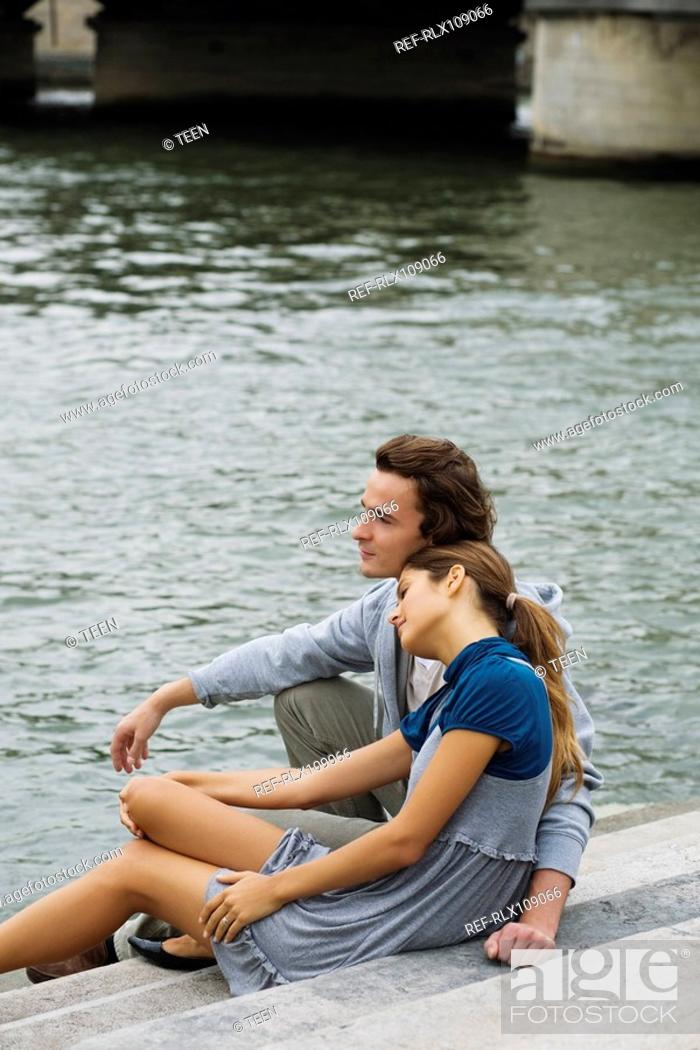 Stock Photo: Young couple sitting on steps by river Seine, Paris, France.