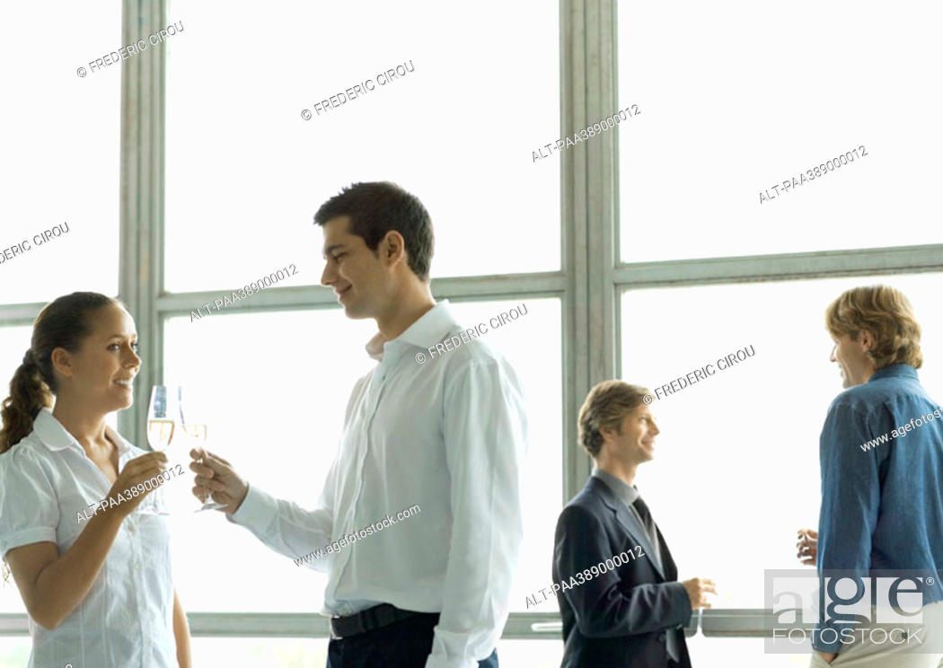 Stock Photo: People talking during office party, holding glasses of champagne.