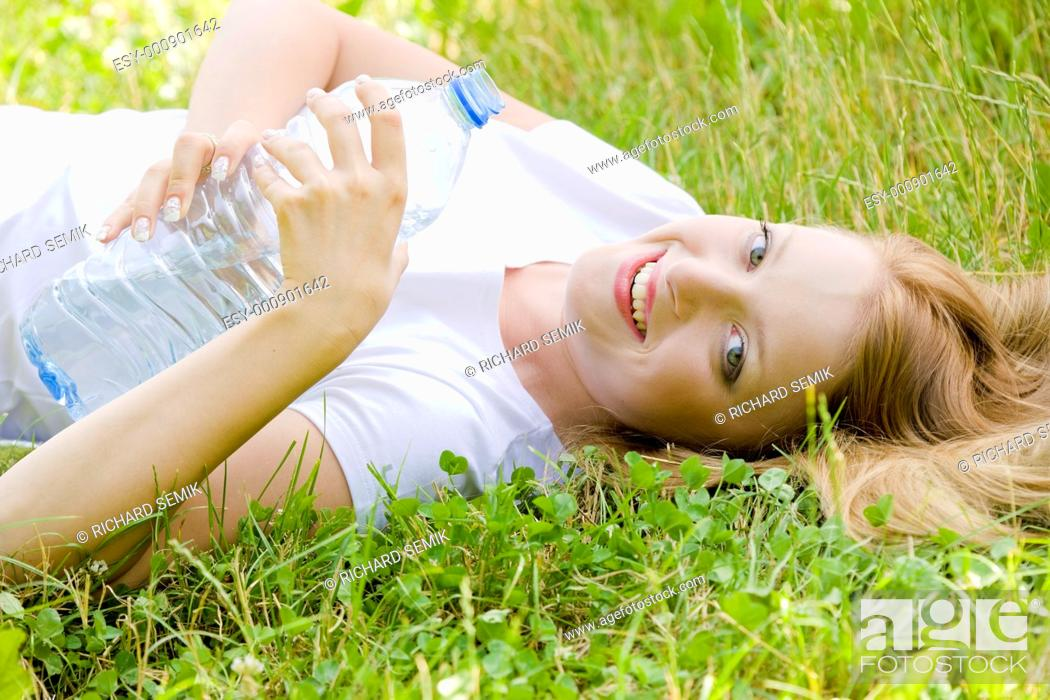 Stock Photo: lying woman with bottle of water.