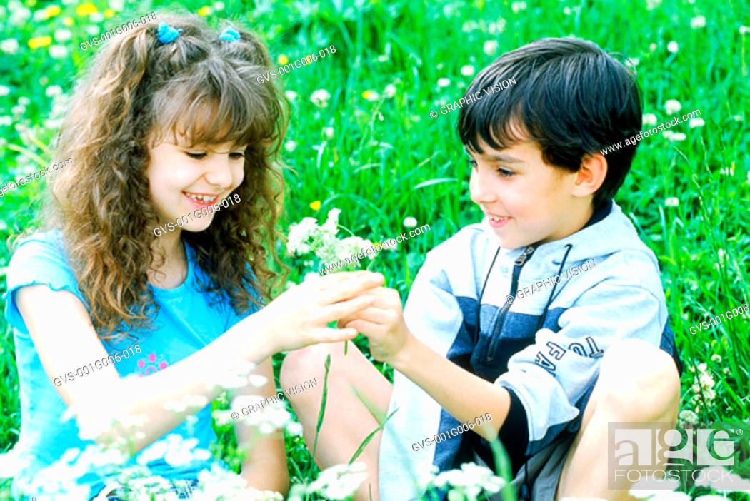 Stock Photo: Boy and girl sitting in a garden together.