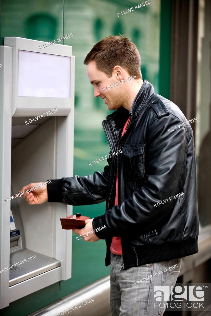 Stock Photo: A young man using a cash machine.