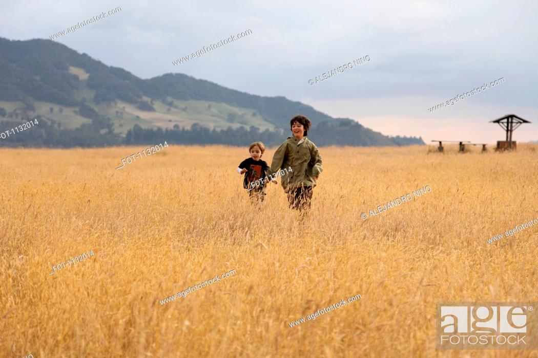 Stock Photo: A teenage boy running with his younger brother in a field.