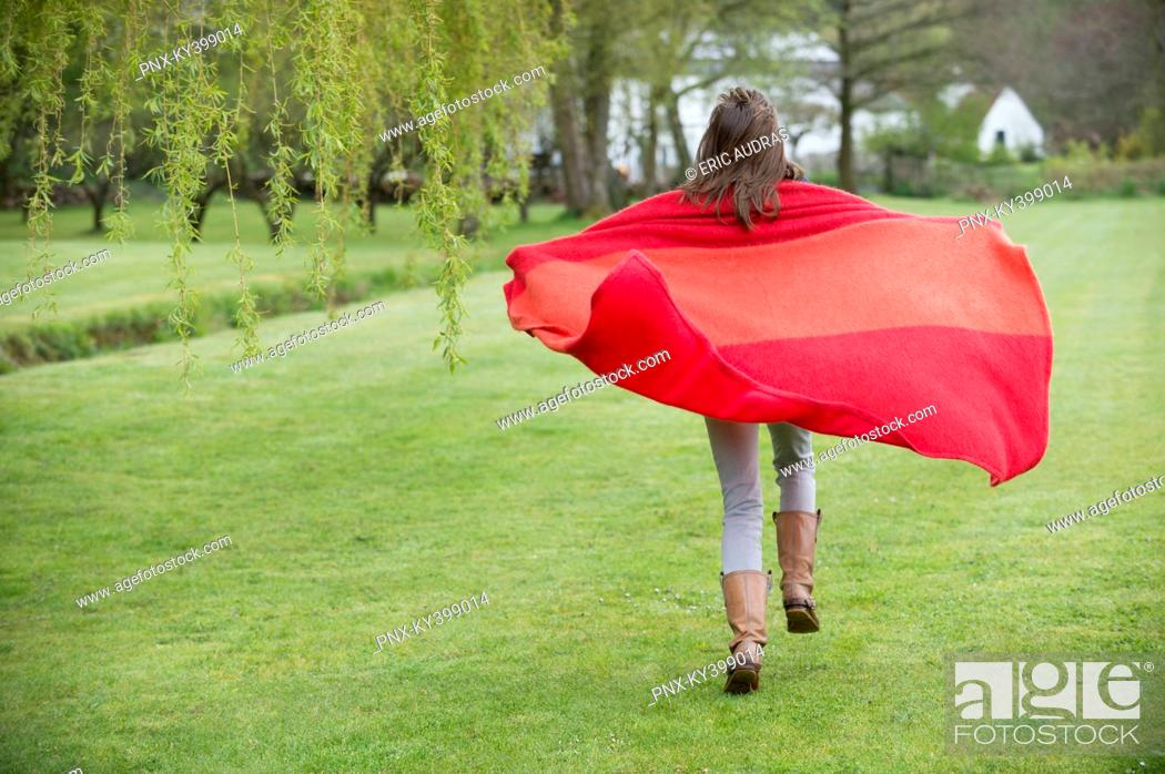 Stock Photo: Girl running in a field with a blanket.