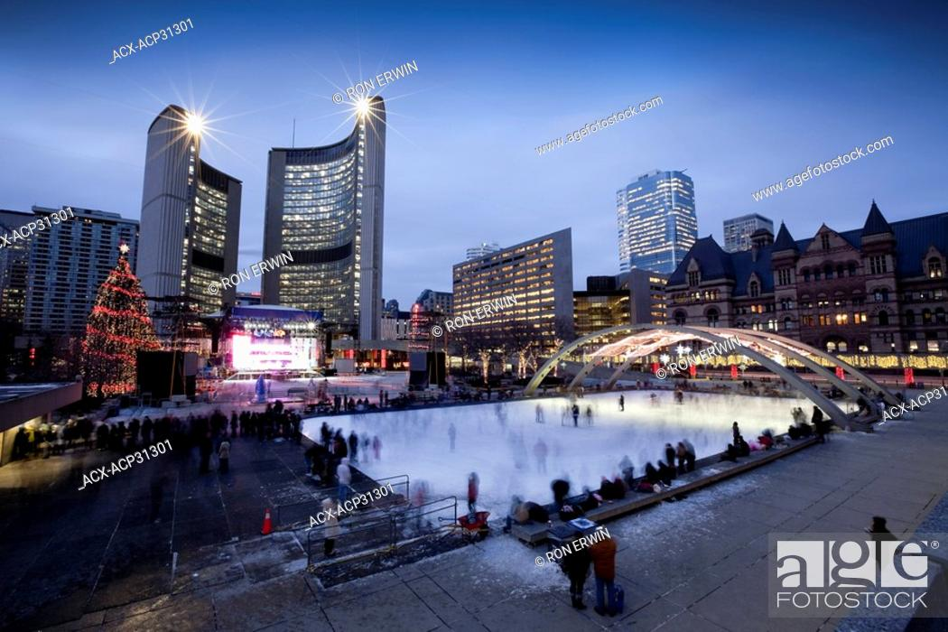 Stock Photo: Evening Skaters outdoors at the Nathan Phillips Square Rink at City Hall in Toronto, Ontario, Canada - a Christmas Tree and stage lit up for the Cavalcade of.