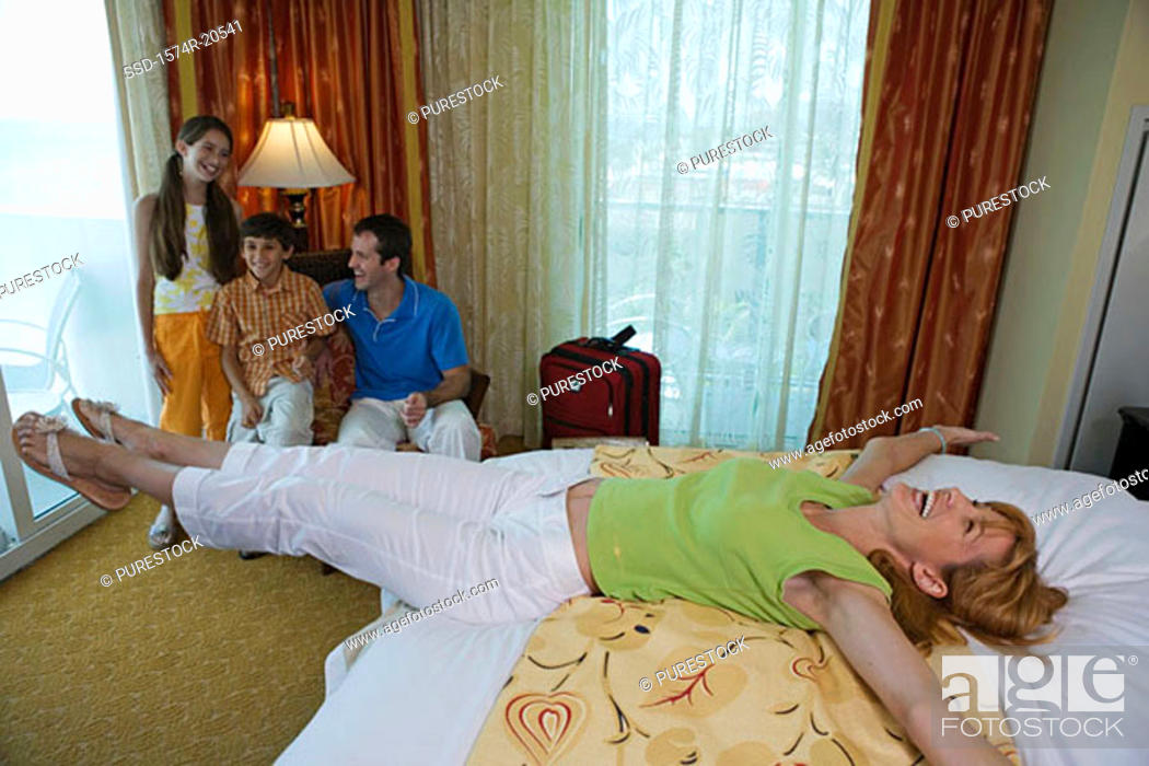 Stock Photo: High angle view of a young couple with their son and daughter in a hotel room.