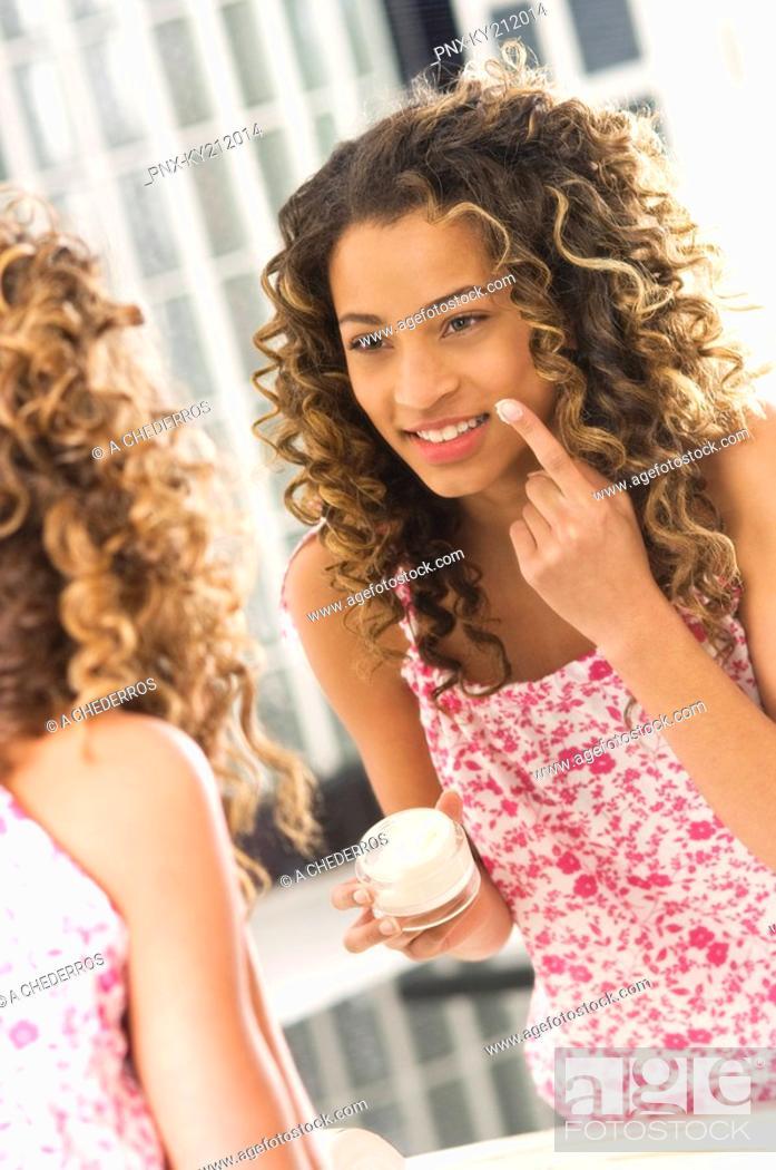 Stock Photo: Girl applying moisturizer on her face.