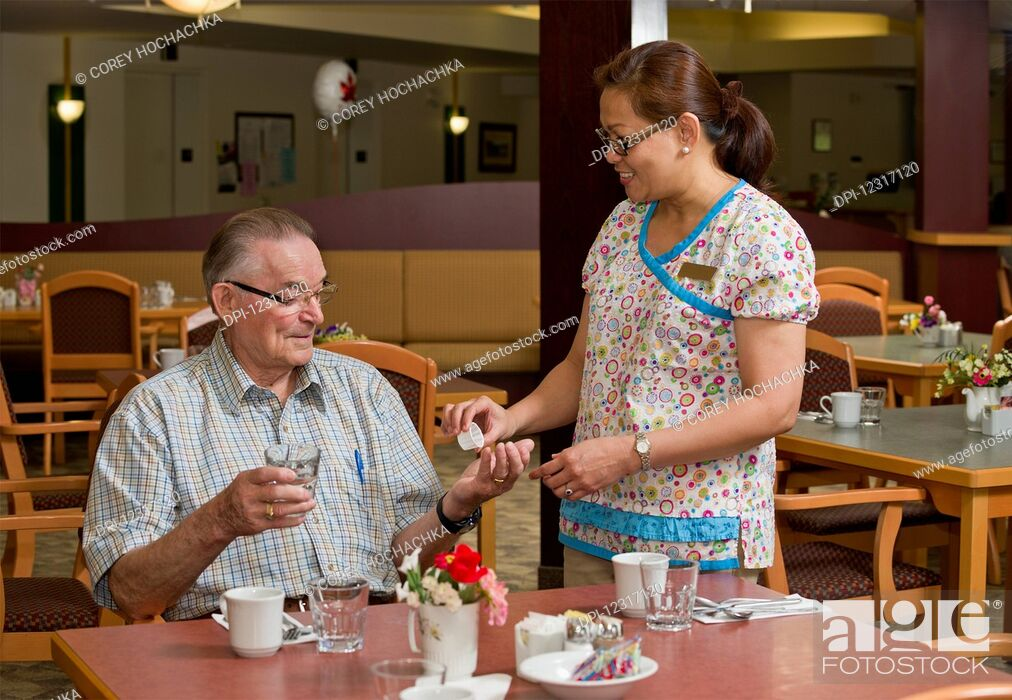 Stock Photo: Senior Citizen Receiving Medication from Caregiver; Devon, Alberta, Canada.