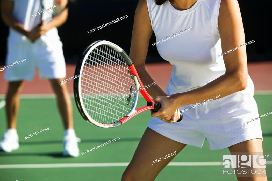 Stock Photo: Mixed doubles tennis players on court focus on woman mid section.
