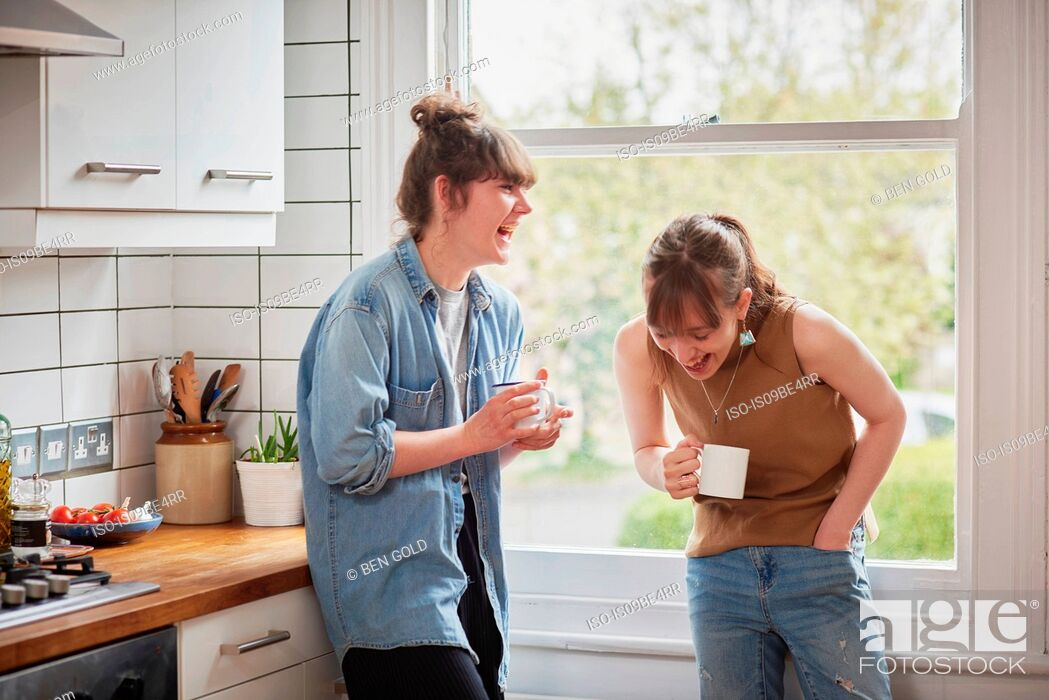 Stock Photo: Friends chatting in kitchen.