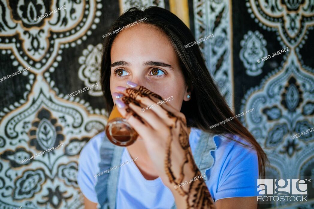 Stock Photo: Morocco, portrait of woman with henna tattoo on her hand drinking glass of tea.
