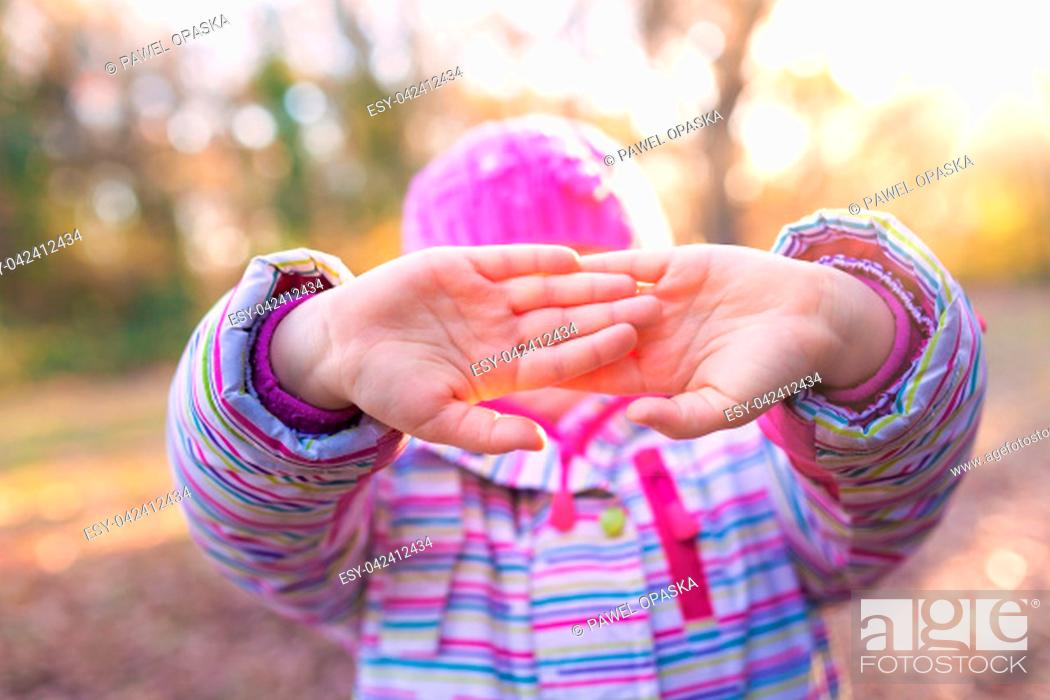 Stock Photo: Portrait of young caucasian girl holding her in front of her face in a gesture suggesting to leave her alone.