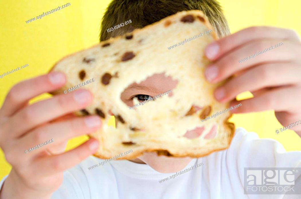 Stock Photo: Boy looking through raisin bread.